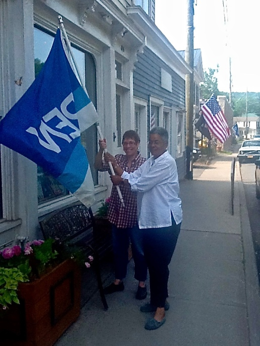 Barbara Balliet and Cheryl Clarke raise the flag at Blenheim Hill Books
